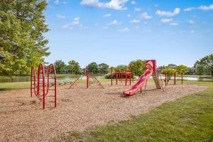 Children's play park with slide, woodchips, and benches with lake in background